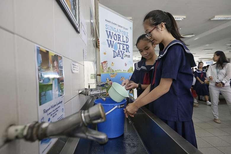 Secondary 2 students Chia Jia En (left) and Koh Wei Shan relying on water in a pail to wash their hands during the water rationing exercise at Woodgrove Secondary School yesterday. Woodgrove is the first of 45 schools, including pre-schools, to conduct the exercise this year.